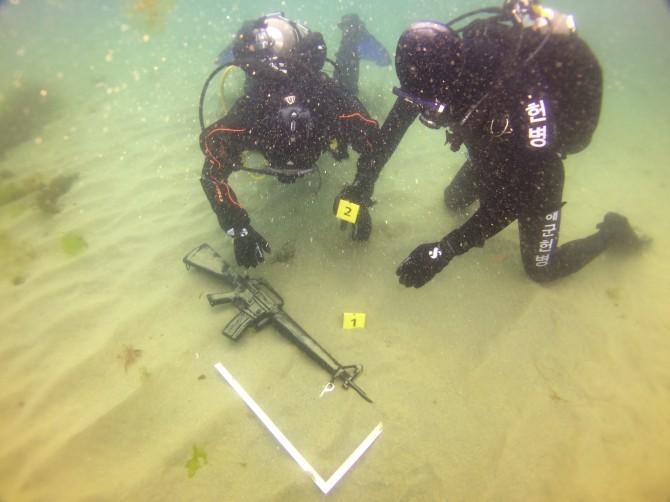 수중과학수사대는 증거물 옆에 삼각자를 놓아 크기를 파악한다 - 해군 제공